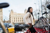 Young chinese woman renting a bicycle in Barcelona — Stock Photo