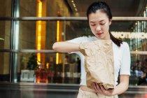 Giovane attraente donna asiatica con sacchetto di carta — Foto stock