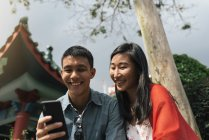 Young asian couple spending time together in city and using smartphone — Stock Photo