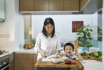 Heureuse jeune asiatique mère et fils, ensemble de cuisine — Photo de stock