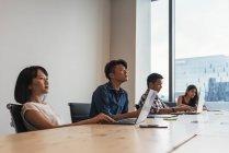 Giovani asiatici uomini d'affari che lavorano insieme in ufficio moderno — Foto stock