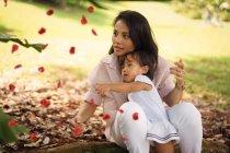 Мило азиатских мать и дочь, играя с листьями в парке — стоковое фото