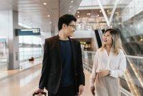 Jovem asiático casal de empresários andando no aeroporto — Fotografia de Stock