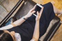 Joven asiática con smartphone en oficina moderna creativa - foto de stock
