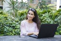 Jovem mulher bonita no seu ar livre portátil — Fotografia de Stock