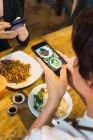 Молода пара беручи продовольство фото в кафе — стокове фото