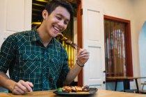 Молоді азіатські людина їсть кебаб в комфортабельних бар — стокове фото