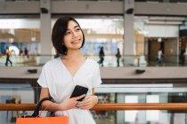 Young beautiful asian woman in shopping mall — Stock Photo