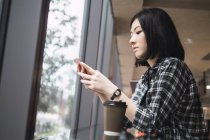 Joven hermosa asiático chica en casual ropa usando smartphone en ciudad calles - foto de stock