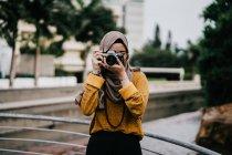 Молодая азиатская мусульманка в хиджабе фотографируется с камерой — стоковое фото