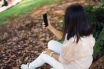 Взрослая азиатка делает селфи в парке — стоковое фото