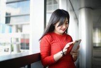 Junge schöne Asiatin mit smartphone — Stockfoto