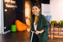 Young asian business woman with scooter in modern office — Stock Photo