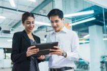 Молоді азіатські бізнесменів за допомогою планшетного ПК у сучасні офісні — стокове фото