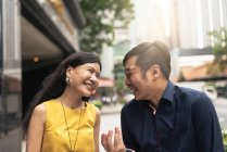Happy young asian couple walking on the street — Stock Photo