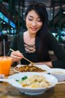 Young asian woman eating food with chopsticks — Stock Photo