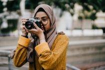 Jeune asiatique femme musulmane en hijab à l'aide de la caméra — Photo de stock