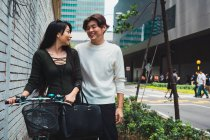 Young asian couple walking on street with bike — Stock Photo