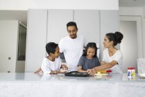 Young asian family celebrating Hari Raya together at home and cooking traditional dishes — Stock Photo