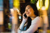 Jovem asiático mulher usando celular no confortável bar — Fotografia de Stock
