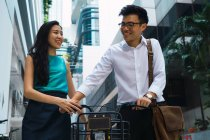 Young adult business couple walking with bicycle — Stock Photo