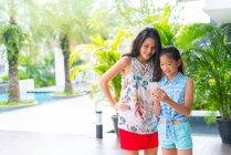 Mutter und Tochter nutzen gemeinsam Smartphone — Stockfoto