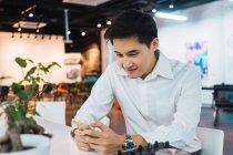 Homem de negócios asiáticos jovens usando smartphone no escritório — Fotografia de Stock