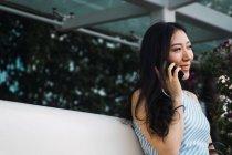 Молодая азиатка говорит по смартфону на открытом воздухе — стоковое фото