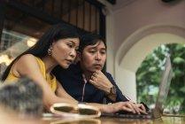 Junge asiatische Brautpaar mit Laptop im café — Stockfoto