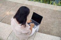 Mujer adulta usando portátil en el parque - foto de stock