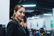 Mujer de negocios asiática joven con smartphone en oficina moderna - foto de stock