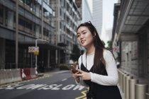 Mujer de cabello largo Chino mirando lejos contra carretera - foto de stock