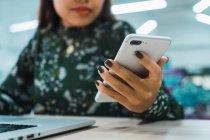 Imagem cortada de mulher de negócios asiática usando smartphone no escritório moderno — Fotografia de Stock