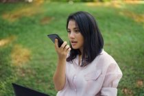 Happy asian woman using smartphone in park — Stock Photo