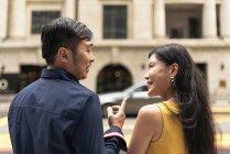 Felice giovane coppia asiatica a piedi sulla strada, l'uomo che punta su qualcosa — Foto stock