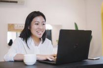 Young asian woman working with laptop in creative modern office — Stock Photo