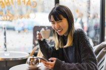 Jovem mulher atraente casual asiática com smartphone e café no café — Fotografia de Stock