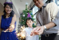 Asian family celebrating Christmas holiday with firework sparklers — Stock Photo