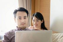 Mature asiatiche coppia casual utilizzando computer portatile insieme — Foto stock
