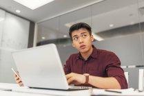 Giovane uomo d'affari asiatico utilizzando laptop in ufficio moderno — Foto stock