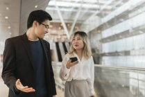 Young asian couple of businesspeople walking in airport — Stock Photo