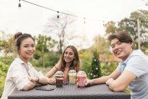 Групи друзів в ресторані, посміхаючись на камеру — стокове фото