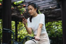 Young attractive asian woman with bike using smartphone — Stock Photo