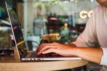 Кадроване зображення людини, використовуючи ноутбук на стіл — стокове фото