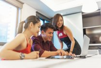 Young attractive asian people working in modern office — Stock Photo
