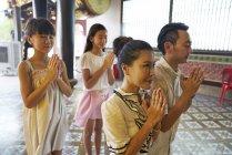 Молодой семьей азиатских молиться в храм — стоковое фото