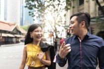 Щасливі молода пара азіатських ходіння по вулиці, вказуючи на те, що людина — стокове фото