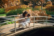 Niedlich asiatisch mutter und tochter looking aus von geländer im park — Stockfoto