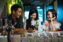 Молодые азиатские друзья в уютном баре — стоковое фото
