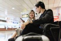 Молодые азиатские пара бизнесменов с смартфон и напиток в аэропорту — стоковое фото